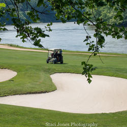golf cart driving past bunker on pete dye river course